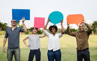 Four people holding speech bubbles